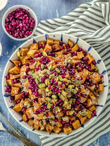 Close up Bird's eye view of a bowl filled with roasted sweet potato cubes topped with Tahini, silan, pistachios and pomegrantes