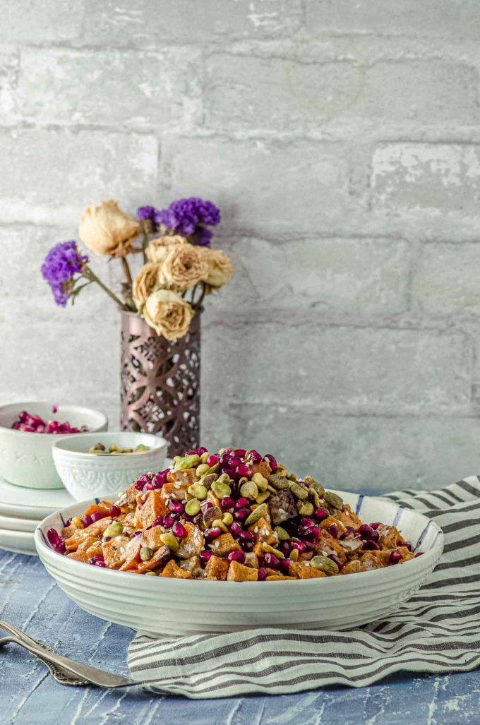 Far side view of a bowl filled with roasted sweet potato cubes topped with Tahini, silan, pistachios and pomegranates