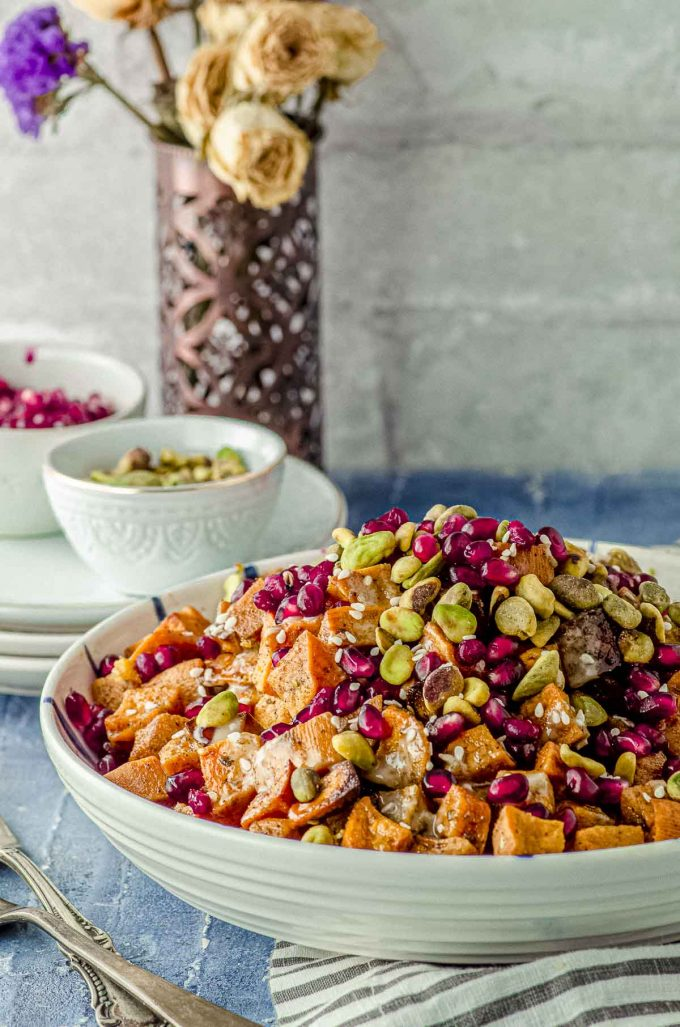 Close up side view of a bowl filled with roasted sweet potato cubes topped with Tahini, silan, pistachios and pomegranates