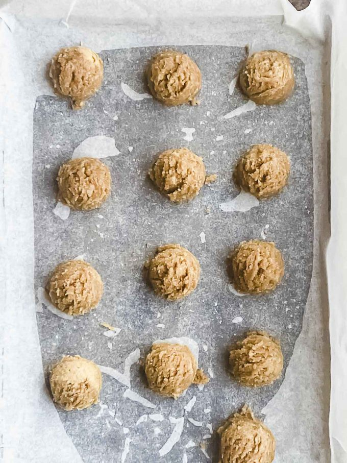 peanut butter cookie dough in balls on a baking sheet