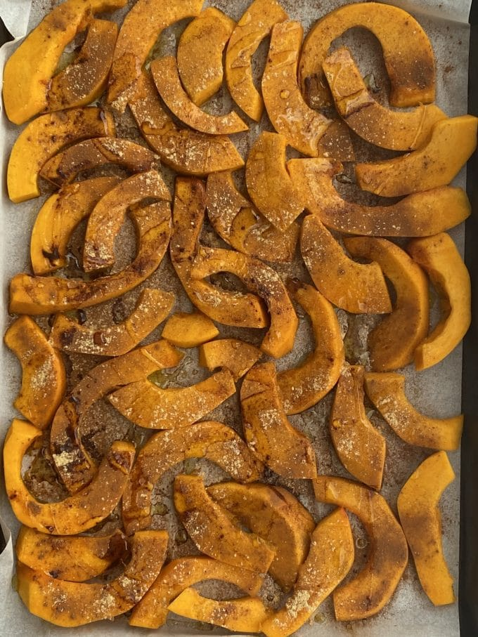 Sliced and peeled thing wedges of pumpkin on a baking sheet