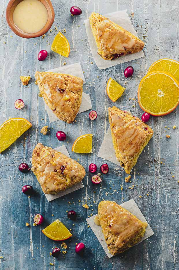 Overhead view of five orange cranberry scones on a blue surface