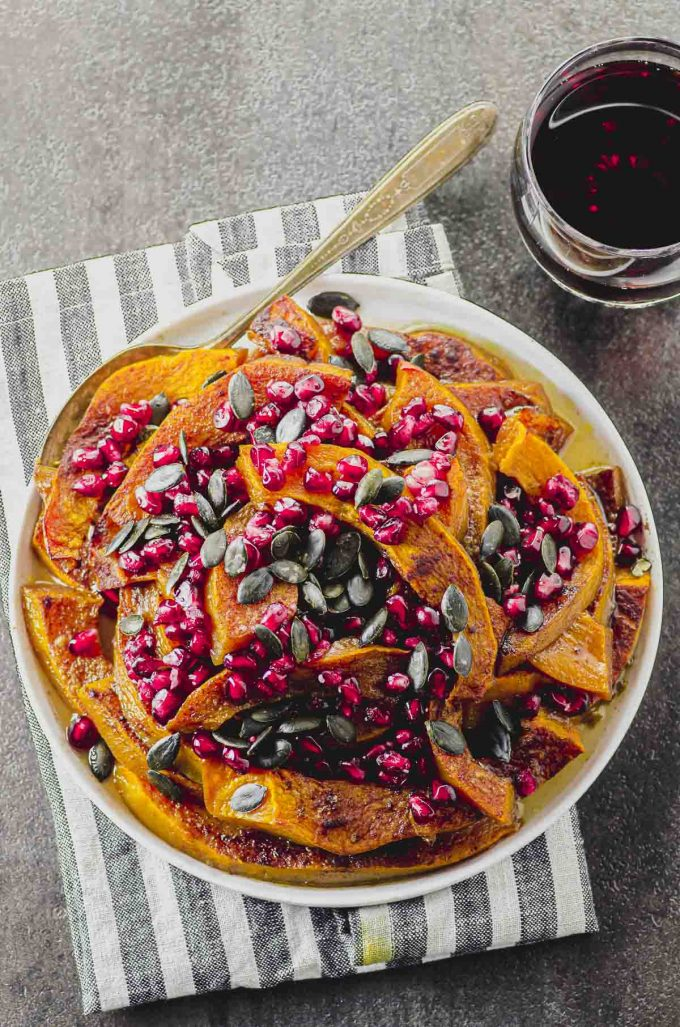 overhead view of a white plate filled with roasted pumpkin and topped with pumpkin seeds and pomegranates seeds