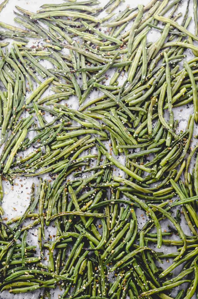 Green beans spread on a baking sheet ready to roast