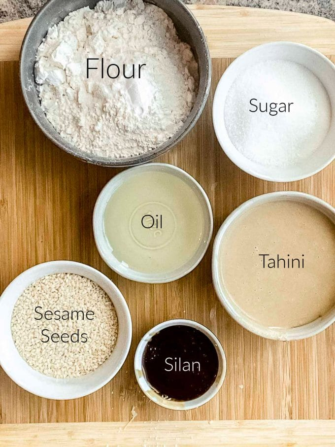 Bird's eye view of the ingredients for tahini cookies. Flour, sugar, oil, tahini, sesame seeds and silan