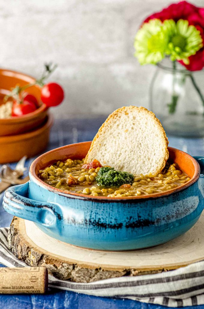 Side view of a blue terra-coat dish with lentil soup and a piece of bread sticking out of the soup