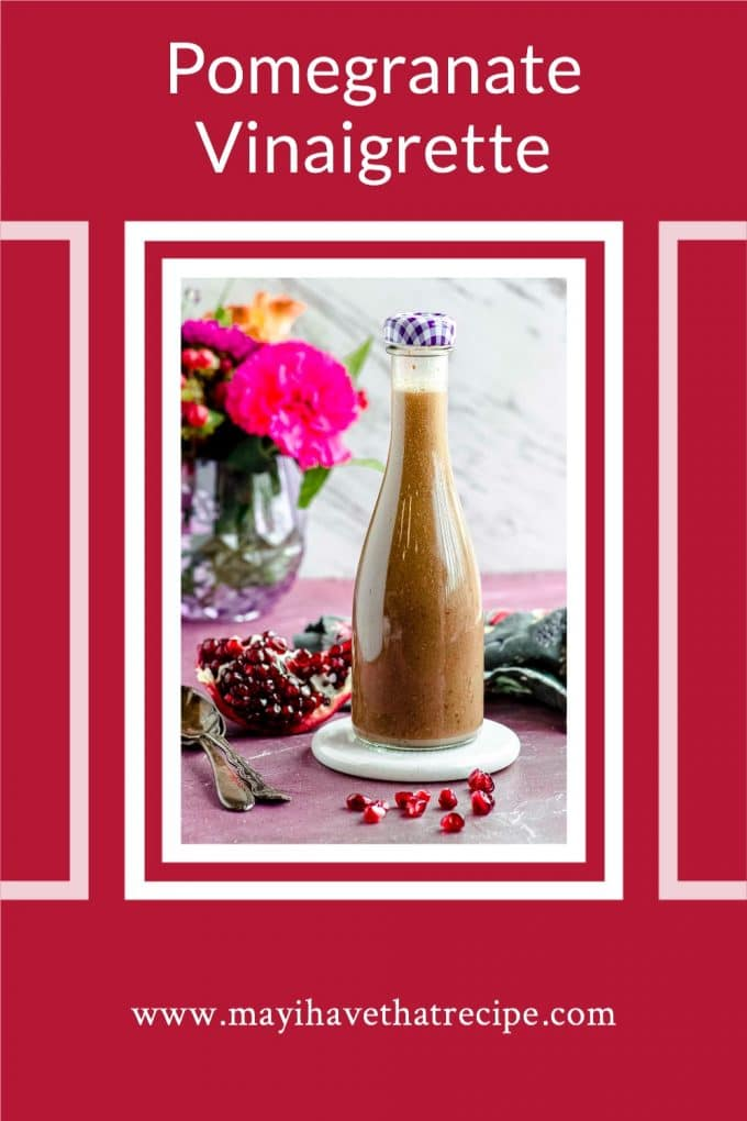 Side view of a glass bottled filled with pomegranate vinaigrette. The image is framed in white with a red background.