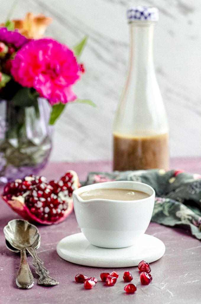 Side view of a small white bowl with pomegranate vinaigrette and a bottle of dressing and flowers in the background