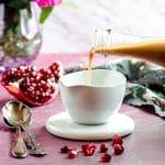 Pouring pomegranate vinaigrette into a small white bowl
