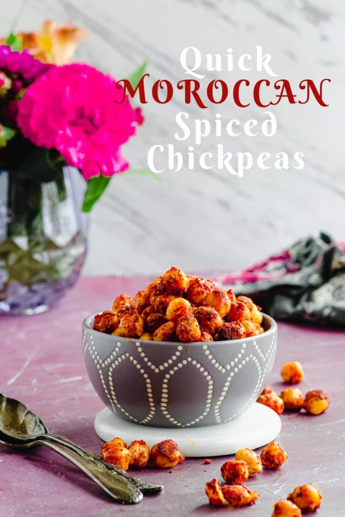 Side view of a grey bowl filled with moroccan spiced chickpeas, with some flowers in a vase in the background with a title