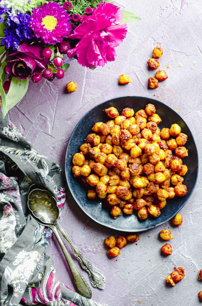 Spiced chickpeas on a black plate, some flowers, a flowery napkin and two spoons
