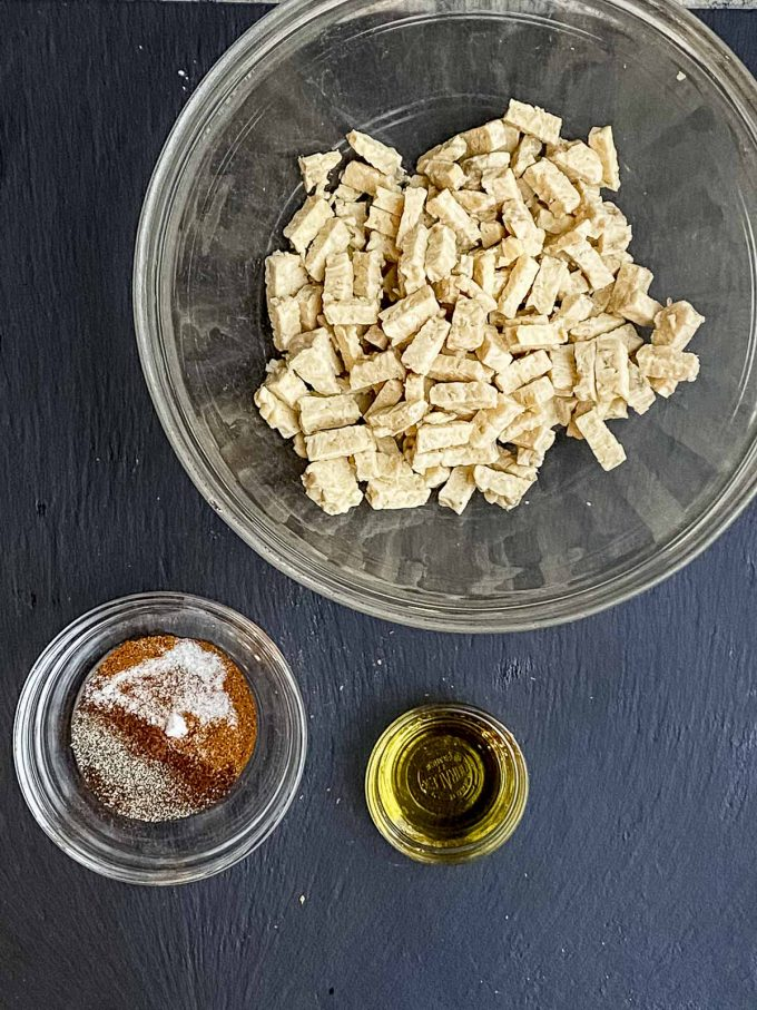 Overhead view of a bowl with pieces of tempeh, a small bowl with olive oil and another small bowl with spices