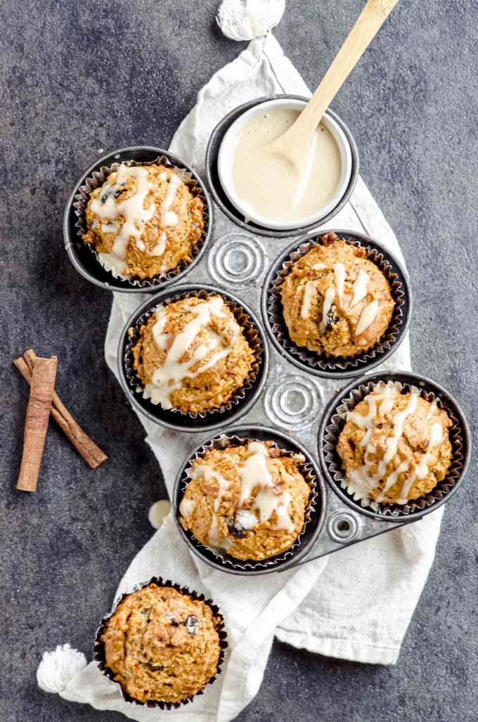 Overhead view of a 6-hole muffin tin with morning glory muffins under a white napkin.