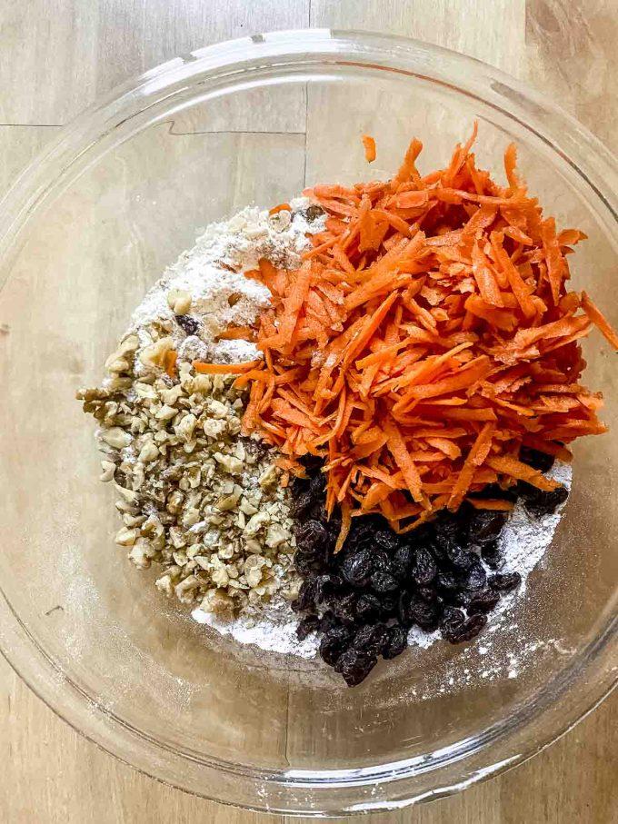Shredded carrots, raisins an walnut in a glass bowl