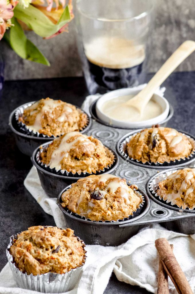 a breakfast scene with one morning glory muffin on the table and 5 muffins inside a muffin tin next to a cup of coffee
