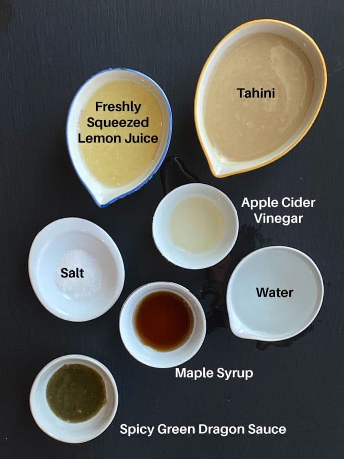 Ingredients to make Spicy tahini dressing labeled: tahini, lemon juice, water, maple syrup, apple cider vinegar, salt and green dragon sauce