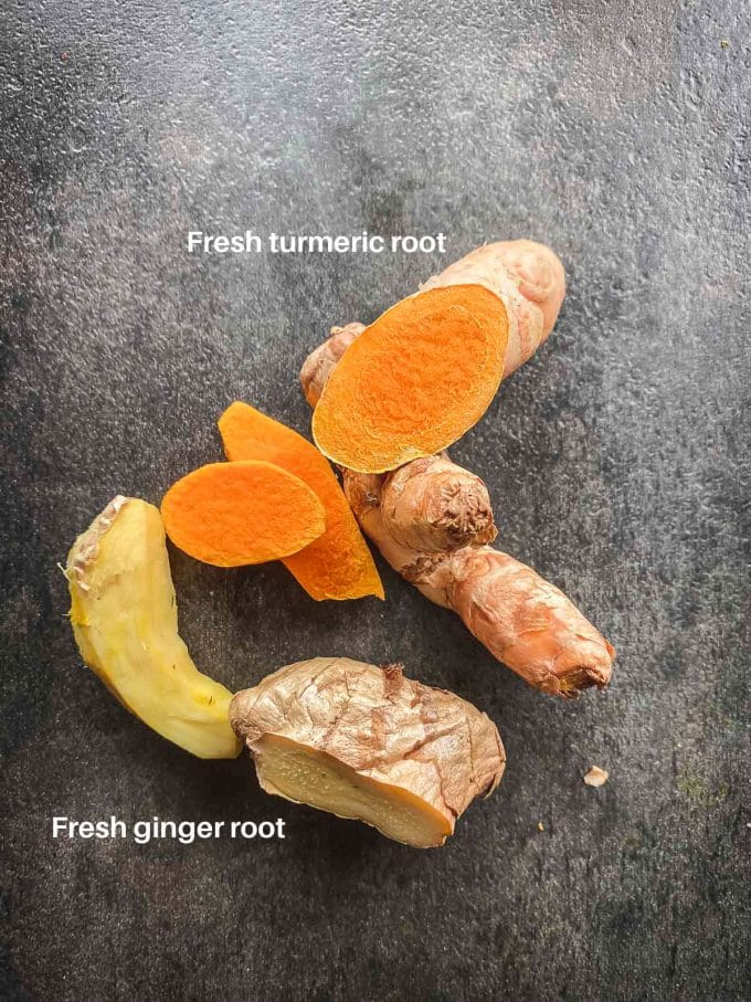 Fresh ginger root and fresh turmeric root on a black surface. Labeled