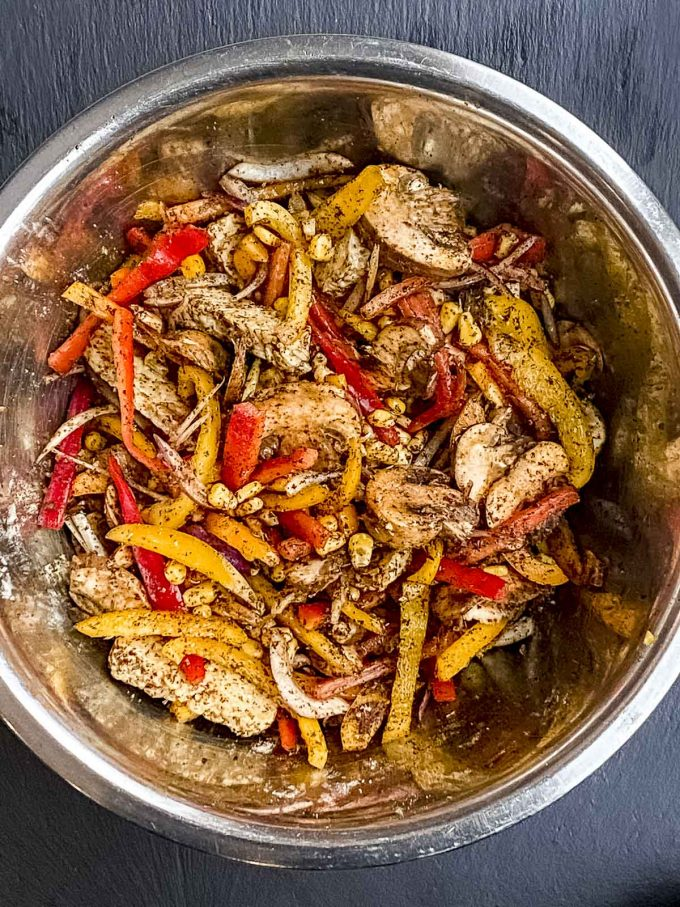 A metal bowl with a  mix veggies, oil and spices