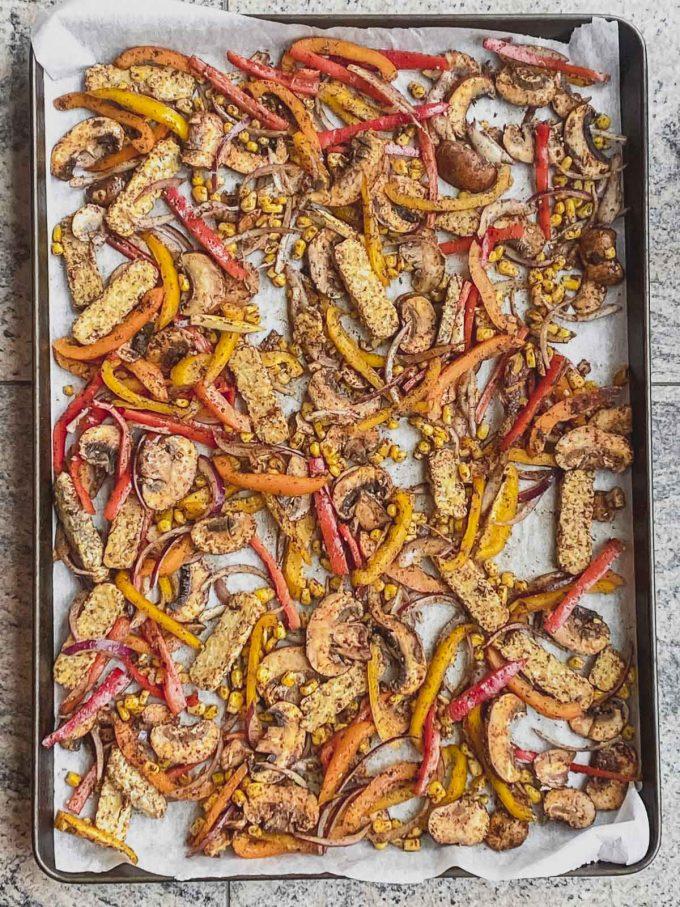 Seasoned vegetables and tempeh on large baking sheet
