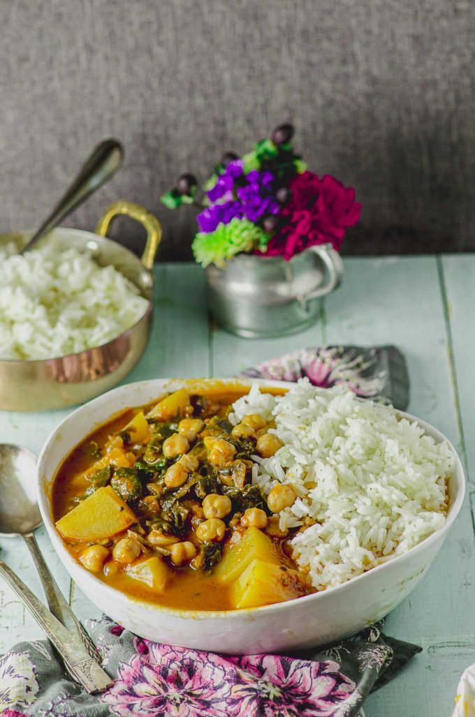 45 degree view of bowl with vegetarian stew and rice, with a bowl of rice and a small vase with flowers in the background