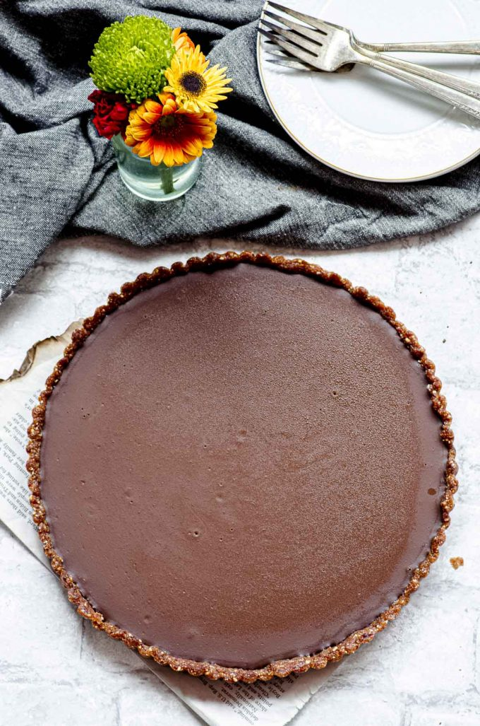 Chocolate tart next to a small vase with flowers and a dark grey napkin