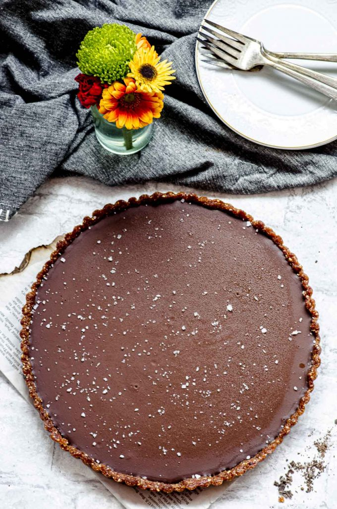 Salted Chocolate tart next to a small vase with flowers and a dark grey napkin