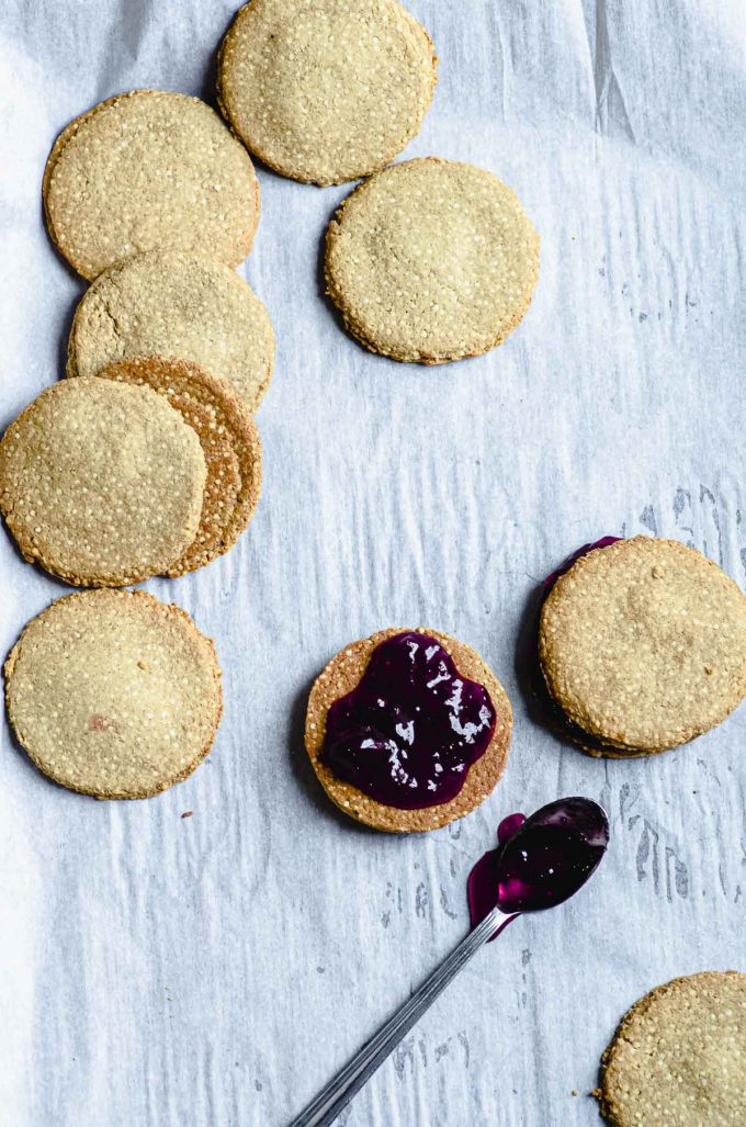 spreading jelly on a quinoa breakfast cookie