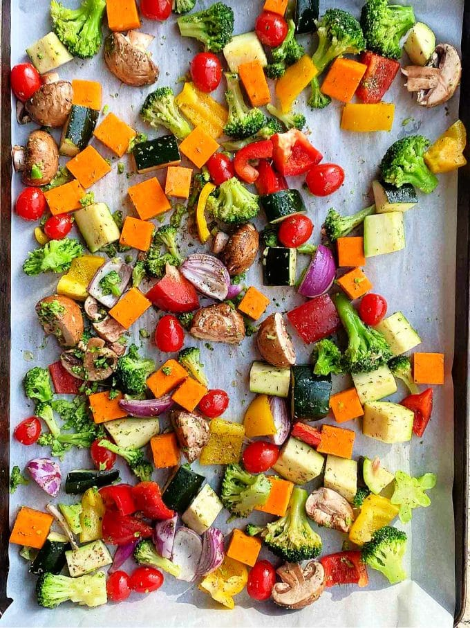 Various raw vegetables on a baking sheet lined with parchment paper.