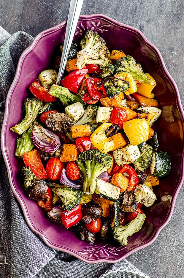 Oven roasted vegetables on a purple serving dish.