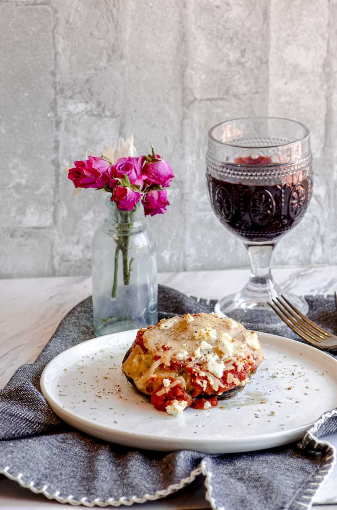A stuffed portobello mushroom on a table with a vase of flowers and a glass of red wine