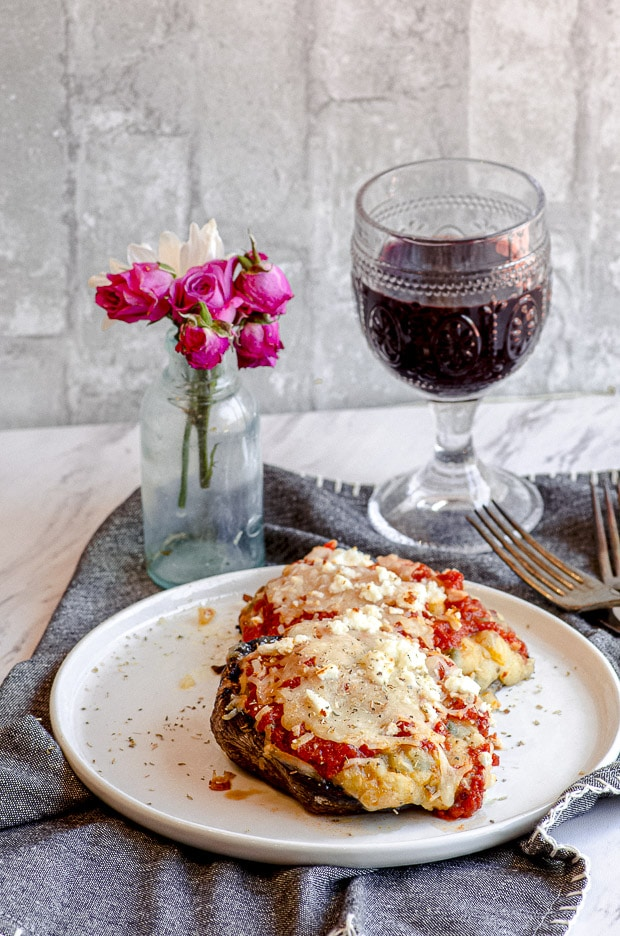 2 Portobello mushrooms on a plate, with red wine on the table