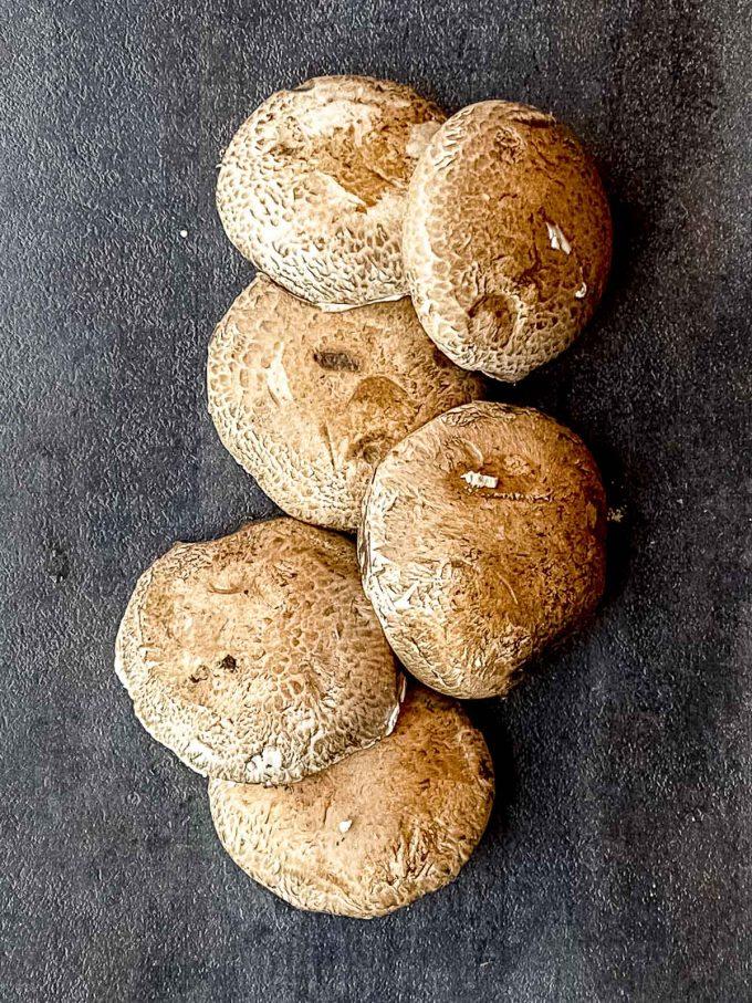 6 raw portobello mushrooms on a black surface