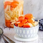 A white and blue bowl filled with pickled carrots and fennel with a jar with the same pickled veggies in the background