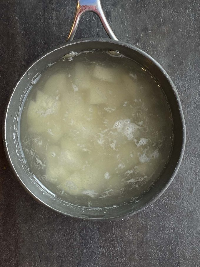 A saucepan filled with water and diced potatoes