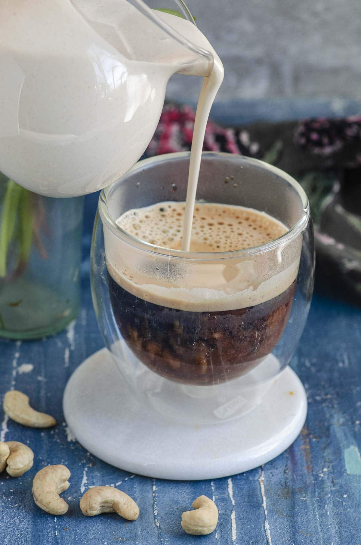 Pouring homemade cashew cream coffee creamer on a cup of coffee