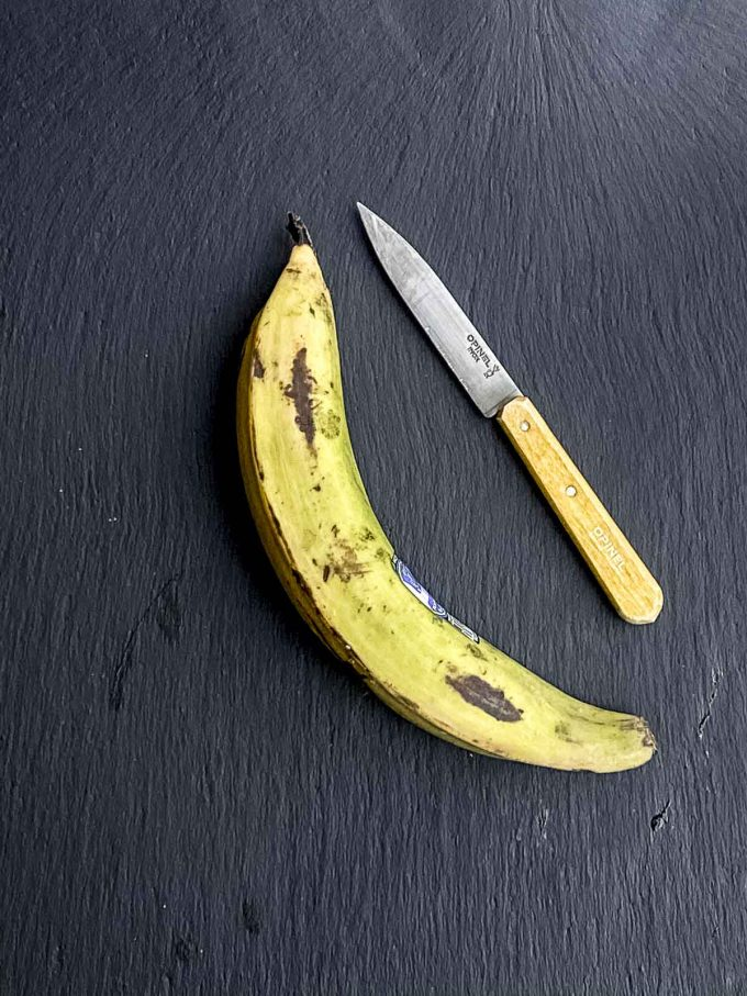 A green plantain on a black surface next to a knife with a yellow handle