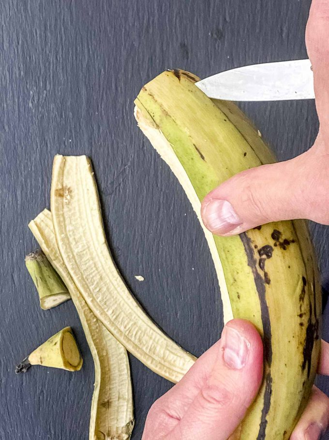 Scoring the skin of a plantain in order to peel it