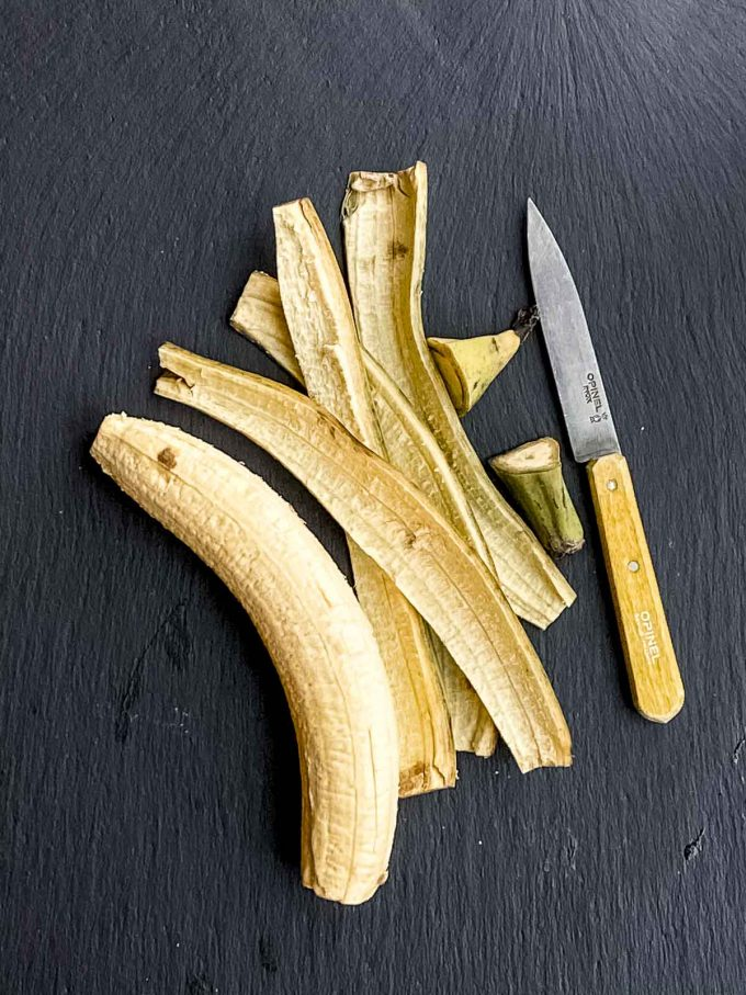 A peel plantain on a black surface next to its peel and a knife with a yellow handle