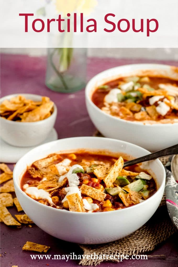 Side view of two white bowls filled with vegetarian tortilla soup and topped with home made tortilla chips.