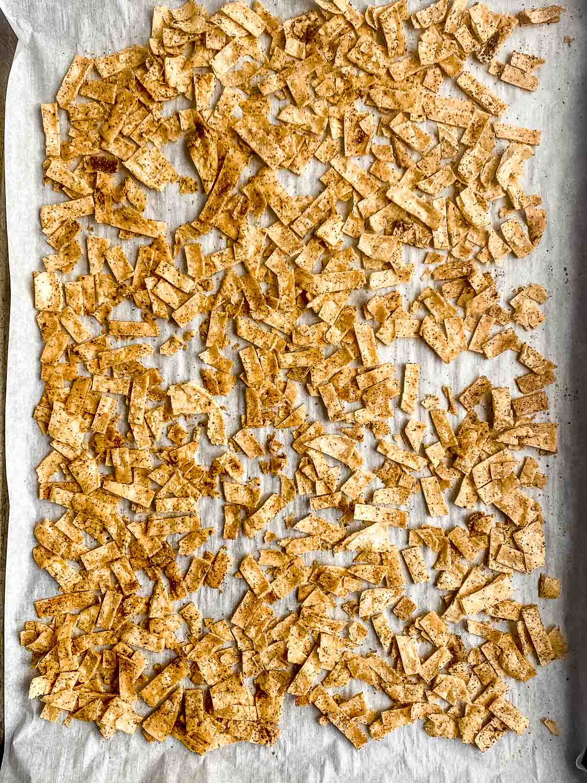 Baked and seasoned corn tortilla chips on a baking sheet lined with parchment paper