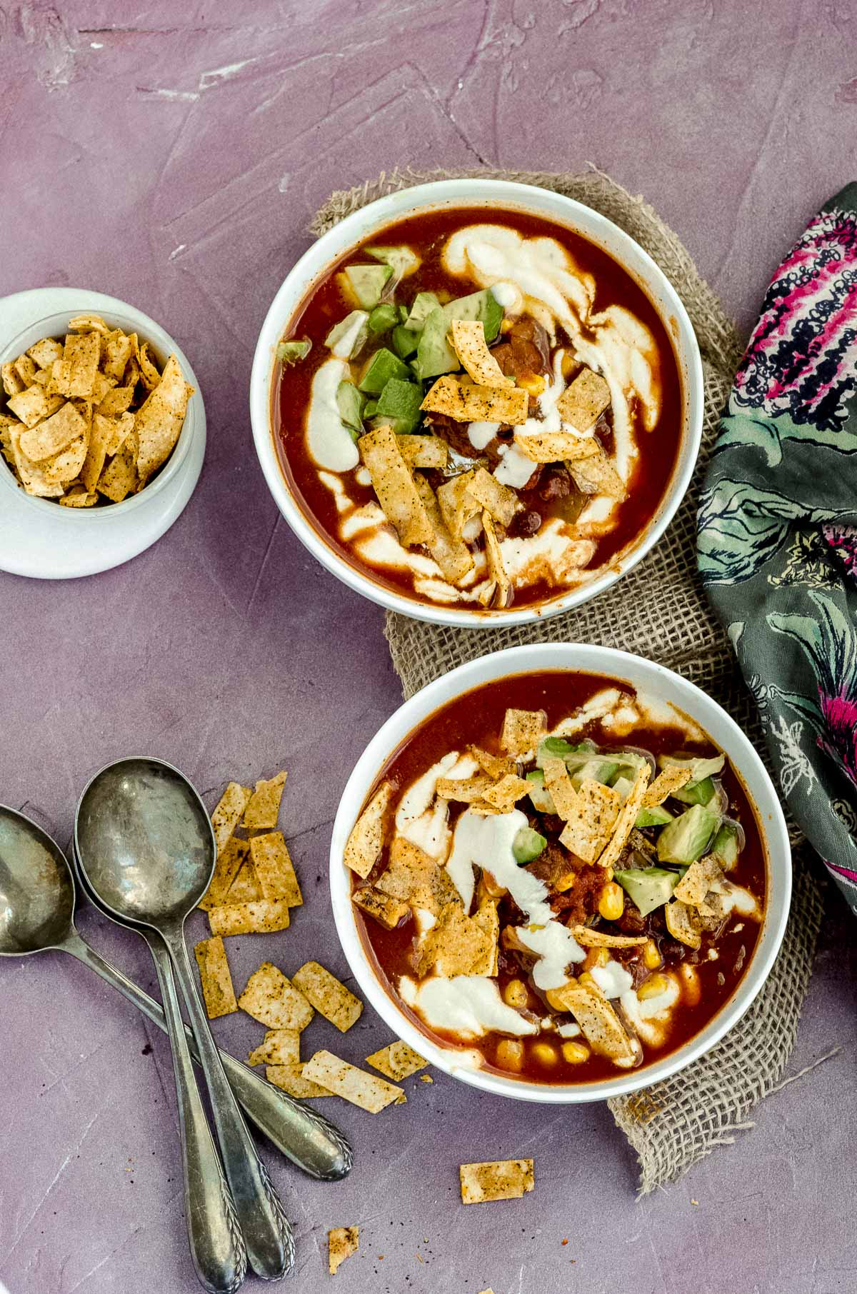 Overhead view of two tortilla soup bowls topped with avocado, tortilla chips and sour cream