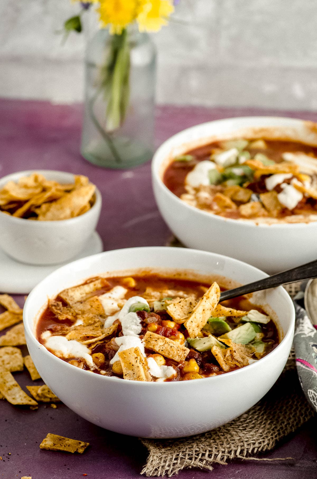 Side view of two white bowls filled with vegetarian tortilla soup and topped with home made tortilla chips