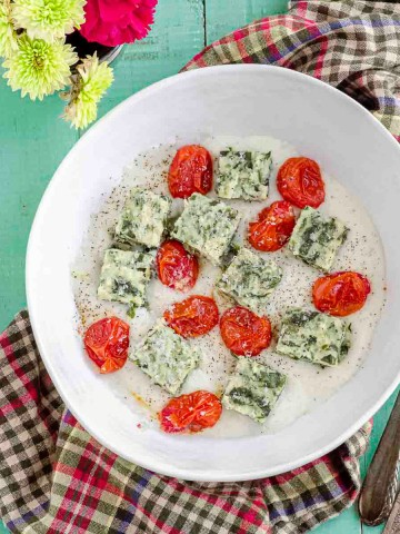Overhead view of a white bowl with spinach semolina gnocchi square over a béchamel sauce and roasted tomatoes