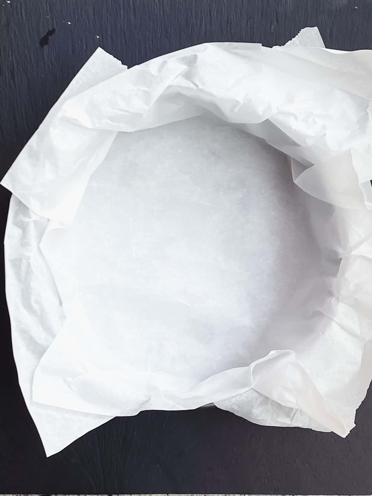 """A 9"""" spring form pan lined with parchment paper"""