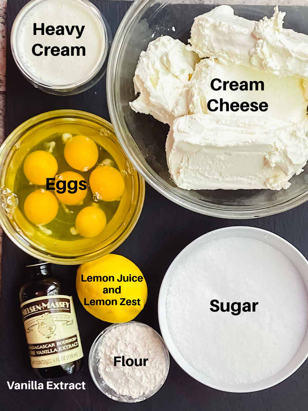 Ingredients for Basque cheesecake labeled: cream cheese, heavy cream, eggs, sugar, lemon, flour and vanilla extract