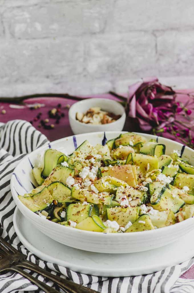Close up side view of a plate with zucchini salad