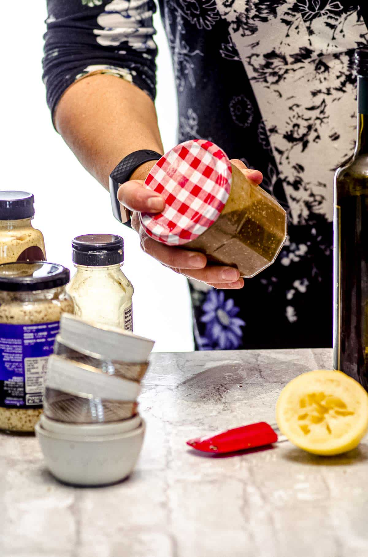 shaking the ingredients of a creamy balsamic dressing in a glass jar.