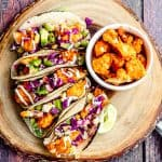 Overhead view of a round wood board with 5 buffalo cauliflower tacos next to a small bowl with buffalo culiflower