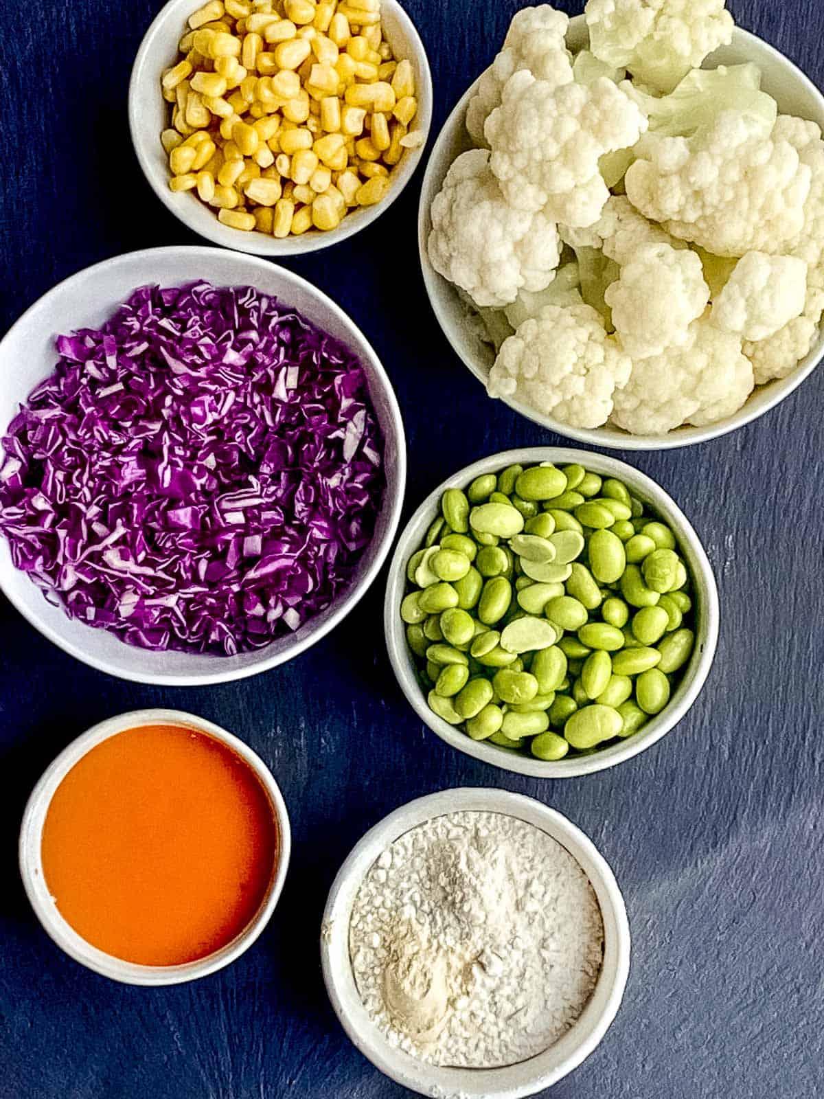 Cauliflower, buffalo sauce, purple cabbage, corn and flour.  The ingredients for make buffalo cauliflower tacos