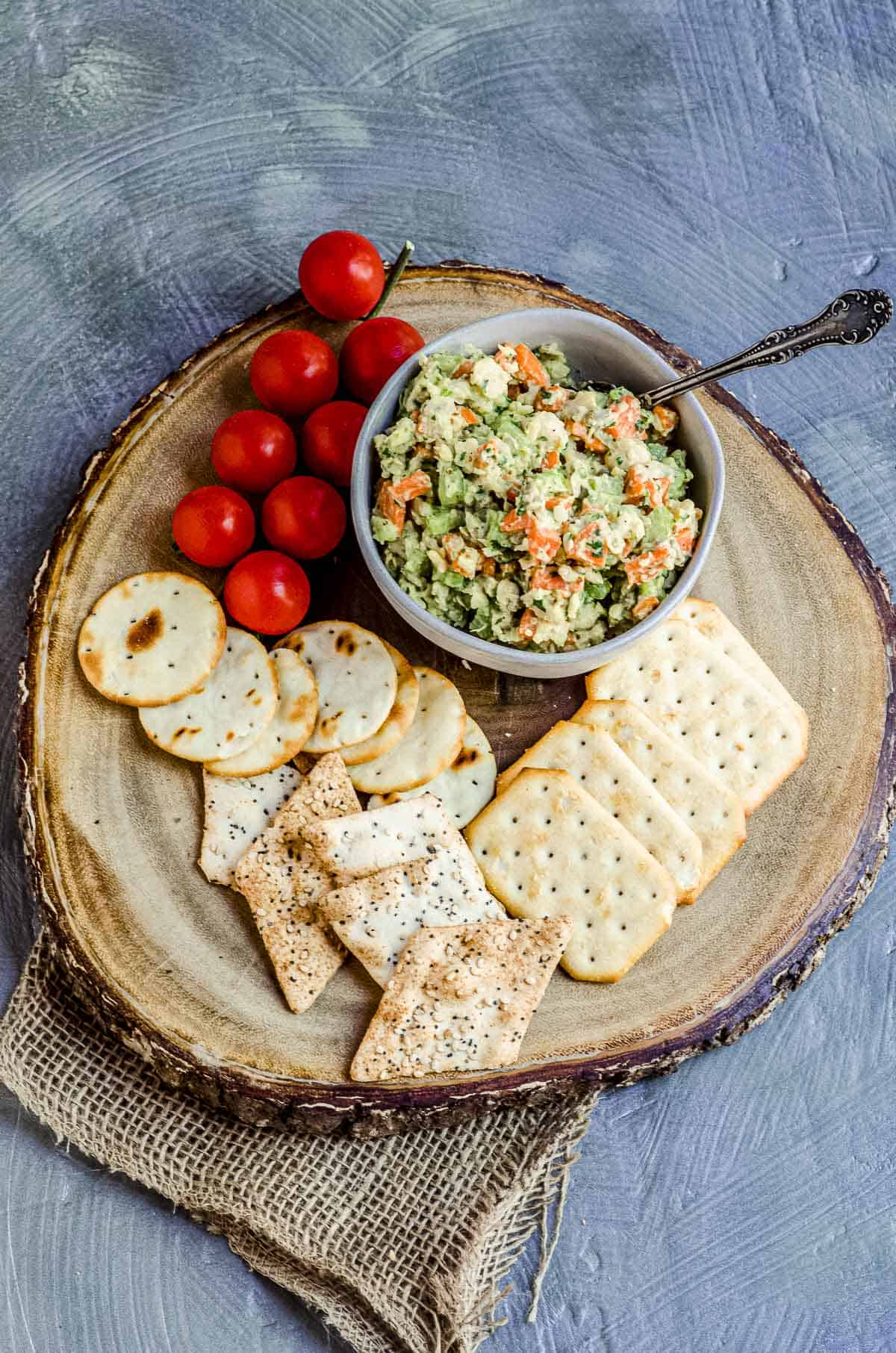 Birdseye view of a bowl with chickpea salad on a wood board with assorted crackers and fresh cherry tomatoes